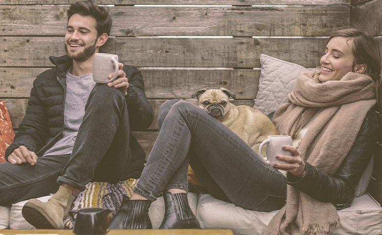 couple with a dog laughing and talking