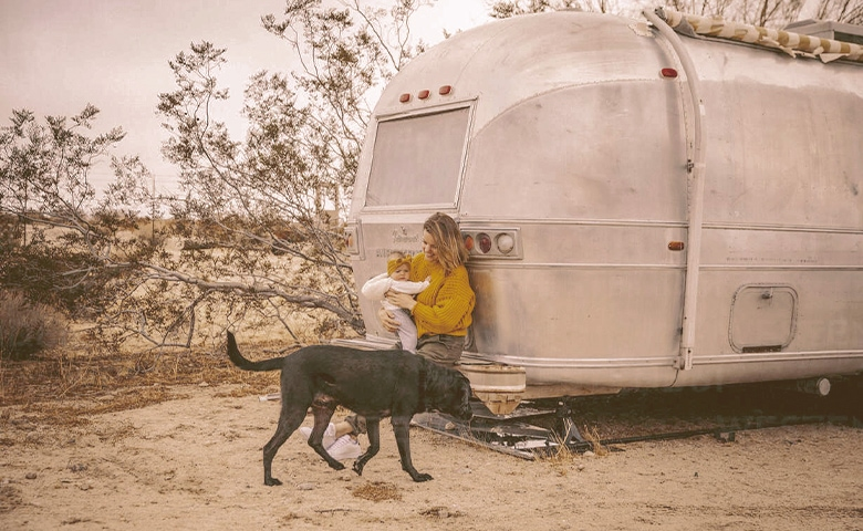 a woman with a baby and a dog near an rv